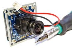Elektronisches Modul mit Linse für Überwachungskamera und Schraubenzieher auf einem weißen Hintergrund Stockfotos