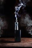 Elektronisk cigarett över en mörk bakgrund Arkivfoto