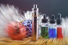 Elektronisk cigarett med vapeflytande inom dunsten och julgarneringar på svart bakgrund suddighet rörelse Royaltyfri Fotografi