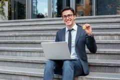 Elektronisk kassa Affärsman i glasögon som sitter på trappa på stadsgatan som arbetar på att le för bärbar datorvisningmynt royaltyfria foton