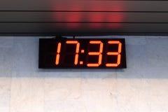 Elektronisk klocka på väggen av byggnadsshowtiden Arkivbild