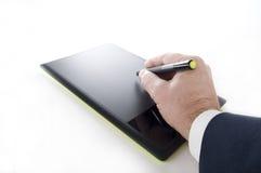 Elektronisk minnestavla och penna med den utövande handen Royaltyfria Foton