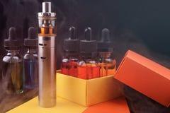 Elektroniska cigarett- och vapeflytande in i den öppnade gåvaasken på fördunklad mörk bakgrund Tonat ljus Arkivfoton