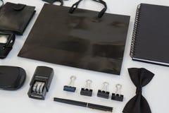Elektroniska grejer och svart hued kontorstillbehör på vit bakgrund Royaltyfri Bild