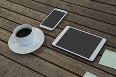 Elektroniska grejer, svart kaffe och klibbig anmärkning på träplanka Fotografering för Bildbyråer