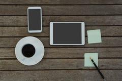 Elektroniska grejer, svart kaffe, penna och klibbig anmärkning på träplanka Royaltyfri Bild