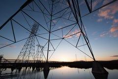 Elektrotorens met belangrijke lijnen bij zonsondergang, met bezinningen in water stock foto's