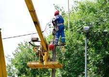 Elektrycy naprawiają druty na słupie z pomocą dźwigowego lifter fotografia stock