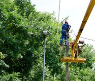 Elektrycy naprawiają druty na słupie z pomocą dźwigowego lifter fotografia royalty free