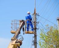 Elektrycy naprawiają linię energetyczną Pracownicy są locksmith elektrykami zdjęcia stock