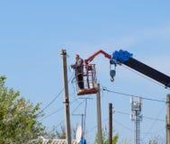 Elektrycy naprawiają linię energetyczną Pracownicy są locksmith elektrykami obrazy royalty free