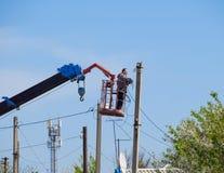 Elektrycy naprawiają linię energetyczną Pracownicy są locksmith elektrykami obraz royalty free