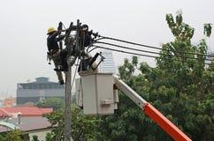 Elektrycy odpoczywa podczas gdy pracujący zamieniać elektrycznego izolator na elektryczność słupie obraz stock