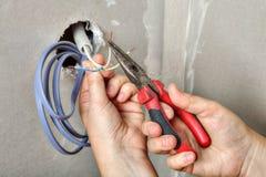 Elektrycy rozjaśniają końcówki druty używać cążki, wręczają zakończenie Obraz Stock