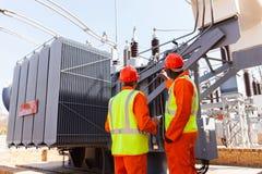 Elektrycy stoi transformator zdjęcia royalty free