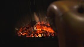 Elektryczna graba z sztucznym lśnienie płomieniem i płonącymi czerwonymi węglami w tle zamazana brąz skóry kanapa zbiory