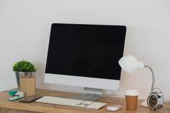 Elektryczna lampa, telefon komórkowy, komputer stacjonarny, rozporządzalny szkło, flory i materiały na stole, obraz stock