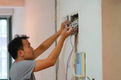 Elektryczna odświeżanie praca, mężczyzna instaluje Przemysłowego elektrycznego wyposażenie Obrazy Stock