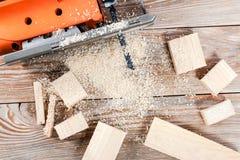 Elektryczna wyrzynarka z wiele drewnianymi cegłami pełno trociny Fotografia Stock