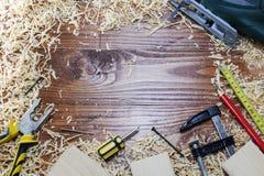 Elektryczna wyrzynarka z wiele drewnianymi cegłami pełno trociny Na starym porysowanym drewnianym stole, praca wytłacza wzory poj Zdjęcie Royalty Free