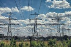 Elektryczne linie energetyczne jako słońce ustawiają w tła błękita naturze fotografia stock