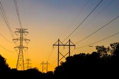 Elektryczne linie energetyczne stoją sylwetkowego pomarańczowym zmierzchem Zdjęcie Stock