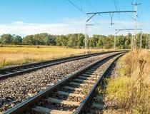 Elektryczne linie kolejowe iść przez wiejskiego krajobrazu Zdjęcie Stock