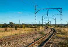 Elektryczne linie kolejowe iść przez wiejskiego krajobrazu Obrazy Stock