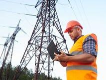 Elektrycznego inżyniera działanie Opowiadać na pracującym wo i telefonie Obrazy Stock