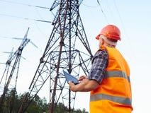 Elektrycznego inżyniera działanie Opowiadać na pracującym wo i telefonie Zdjęcia Royalty Free