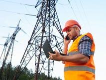 Elektrycznego inżyniera działanie Opowiadać na pracującym wo i telefonie Zdjęcie Royalty Free