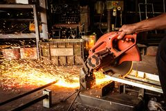 Elektrycznego ostrzarza tnąca stal Pracujący mężczyzna z elektrycznym ostrzarza narzędziem w fabryce z pożarniczymi iskrami fotografia stock