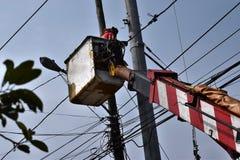 Elektryczni pracownicy instaluje Wysokiego napięcia druty na wysokim betonowym poczta spodzie Na Telehandler Z wiadrem przeglądaj Zdjęcia Royalty Free