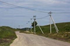 Elektryczni słupy i drogowy znak wzdłuż wiejskiej drogi Obraz Stock