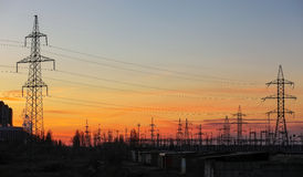 Elektryczność linie energetyczne przy zmierzchem i pilony Zdjęcie Stock