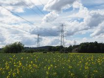 Elektryczność pilony w polu rapeseed, przeciw chmurnemu niebieskiemu niebu obraz stock