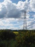 Elektryczność pilony w polu z chmurnym niebieskim niebem obrazy stock