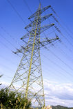 Elektryczność pilony z elektrycznymi drutami i niebieskim niebem Obrazy Royalty Free