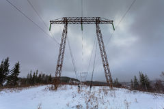 Elektryczność przekazu linie energetyczne na zimy tła Wysokim woltażu górują Metal elektryczności przekazu pilon Zdjęcie Stock