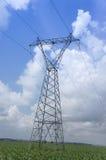 Elektryczności pilonu skrzyżowanie wzdłuż pola. Obrazy Stock