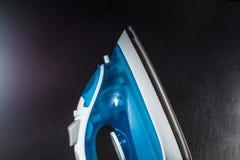 Elektryczny błękita żelazo z białym kolorem Nowożytni mali urządzenia dla domu prasowanie Czarny tło obrazy stock