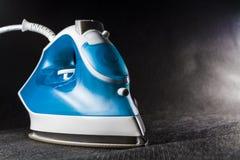 Elektryczny błękita żelazo z białym kolorem Nowożytni mali urządzenia dla domu prasowanie Czarny tło zdjęcie stock