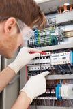 Elektryczny inżynier egzamininuje fusebox z multimeter sondą Obraz Stock