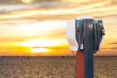 Elektryczny pojazd ładuje Ev stację z prymką władza kabla dostawa dla Ev samochodu na morzu i wschód słońca tle fotografia stock
