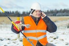 Elektryczny pracownik z telefonem komórkowym blisko tensioner obrazy stock
