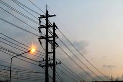 Elektryczny słup władzy gmatwaniny drutu niebezpieczeństwo, druciana elektryczna energia i światło przy uliczną drogą na nieba tł Zdjęcia Royalty Free
