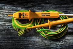 Elektryczny testra kawał chłopa staczająca się kablowa elektryk taśma na drewnianym obraz royalty free