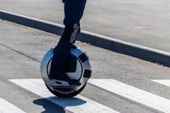 Elektryczny Unicycle M??czyzna jedzie na mono kole na zebry skrzy?owaniu zdjęcia stock