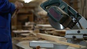 Elektryczny zobaczył dla piłować deski, pracownik piły drewniana deska w warsztacie zbiory