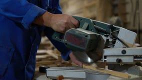 Elektryczny zobaczył dla piłować deski, pracownik piły drewniana deska w warsztacie zbiory wideo